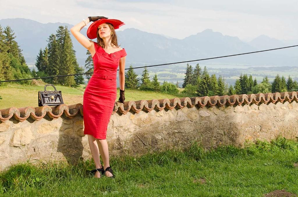 RetroCat im roten Kleid mit Bergen im Hintergrund