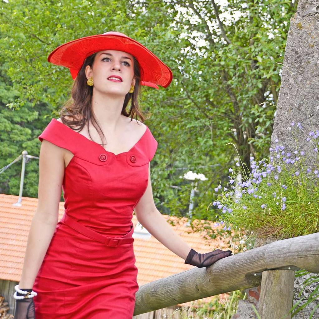RetroCat mit Glitter Paradise Ohrringen und rotem Kleid vom Collectif