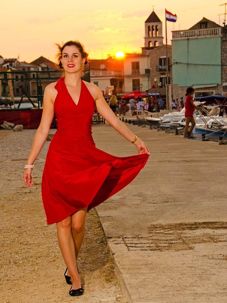 RetroCat in einem roten Neckholder-Kleid am Hafen von Vodice
