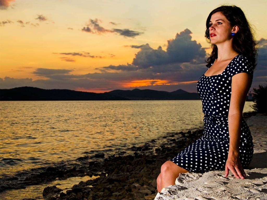 RetroCat im Kleid mit Polka-Dot-Muster vor dem Sonnenuntergang