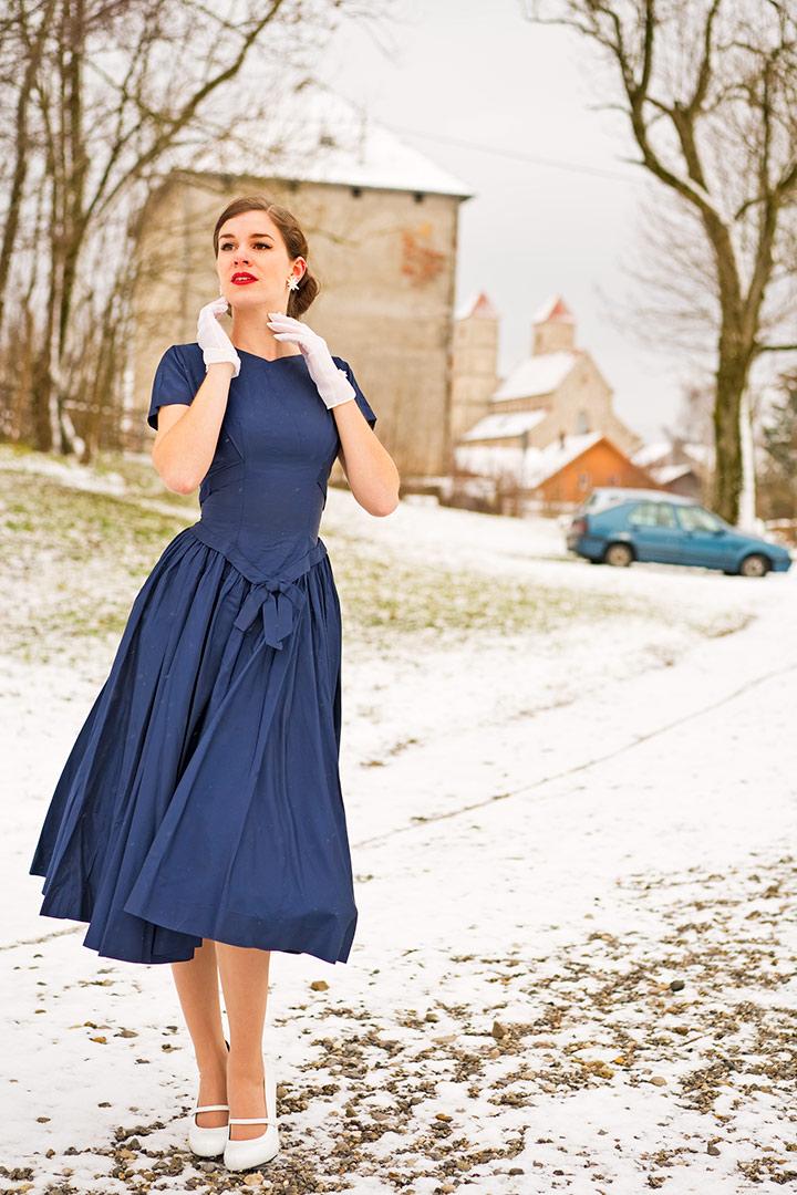 RetroCat in einem Vintage-Kleid mit weißen Accessoires
