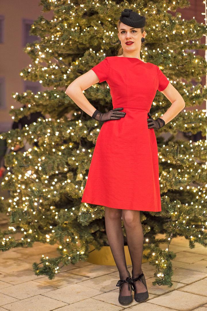 RetroCat im roten Vintage-Kleid vor einem Weihnachtsbaum