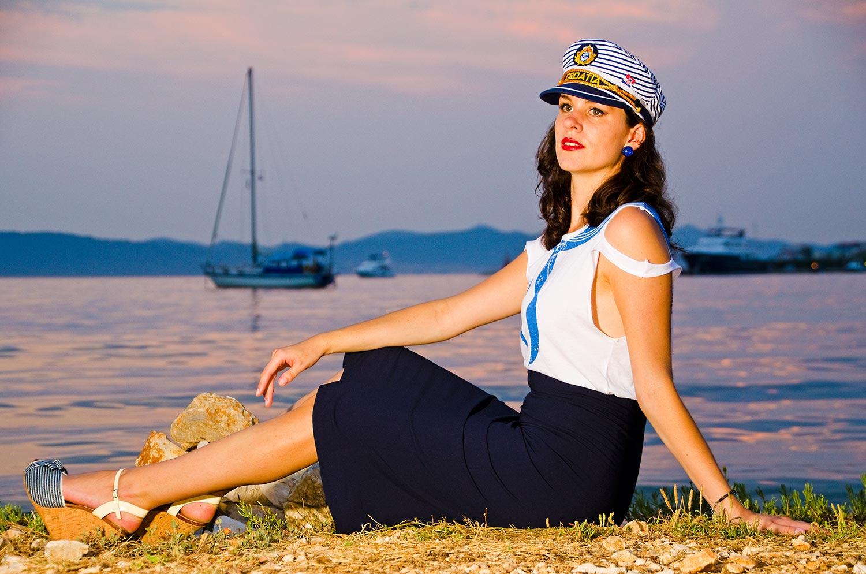 RetroCat in einem maritimen Outfit vor einem Segelboot