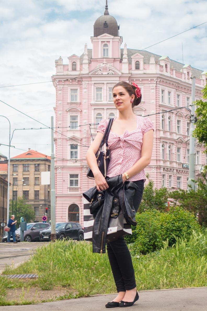 RetroCat mit Retro-Bluse und schwarzer Hose vor einem rosa Haus