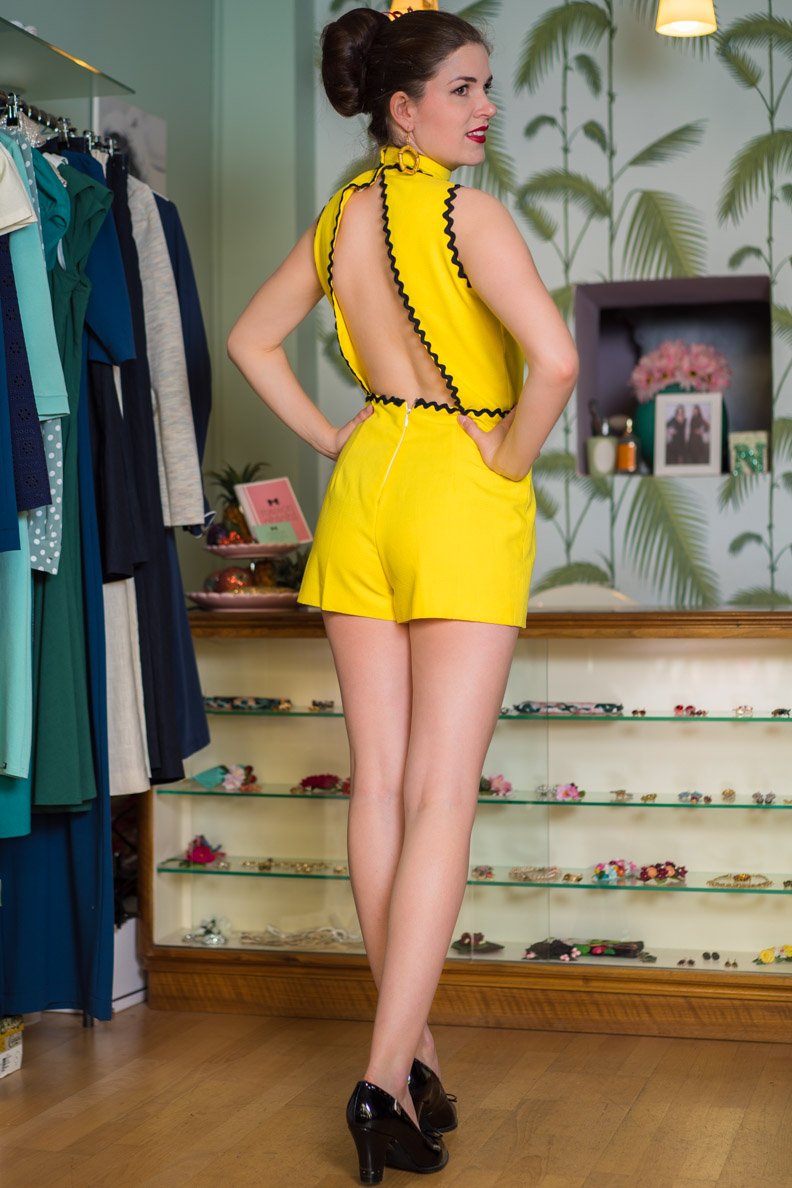 RetroCat in einem gelben Vintage-Jumpsuit mit Rückenausschnitt