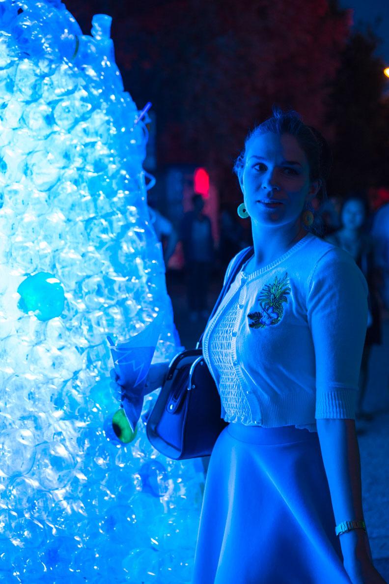 RetroCat vor einem blau beleuchteten Kunstwerk aus alten Flaschen