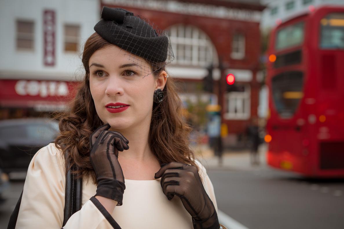 Fashion-Bloggerin RetroCat mit Hut, Handschuhen und schwarzen Ohrringen