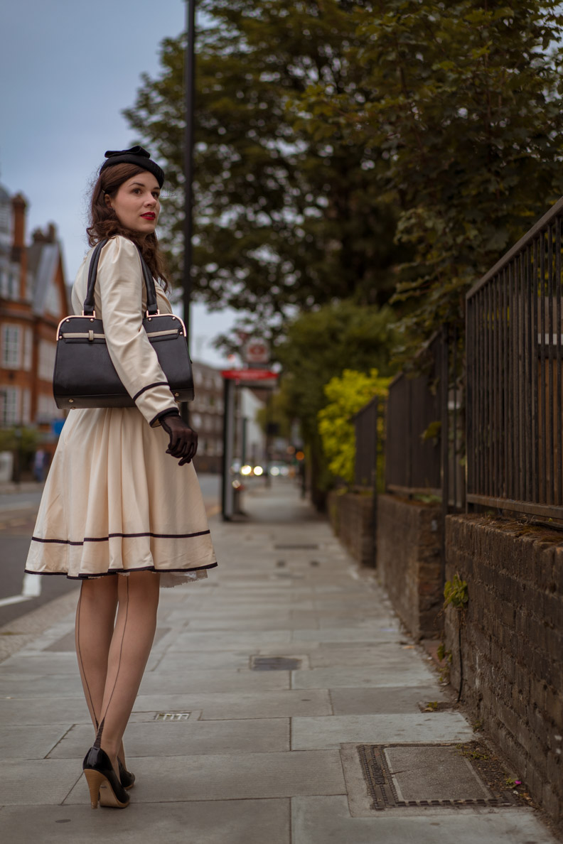 Vintage-Bloggerin RetroCat in einem hellen Kleid mit langen Ärmeln