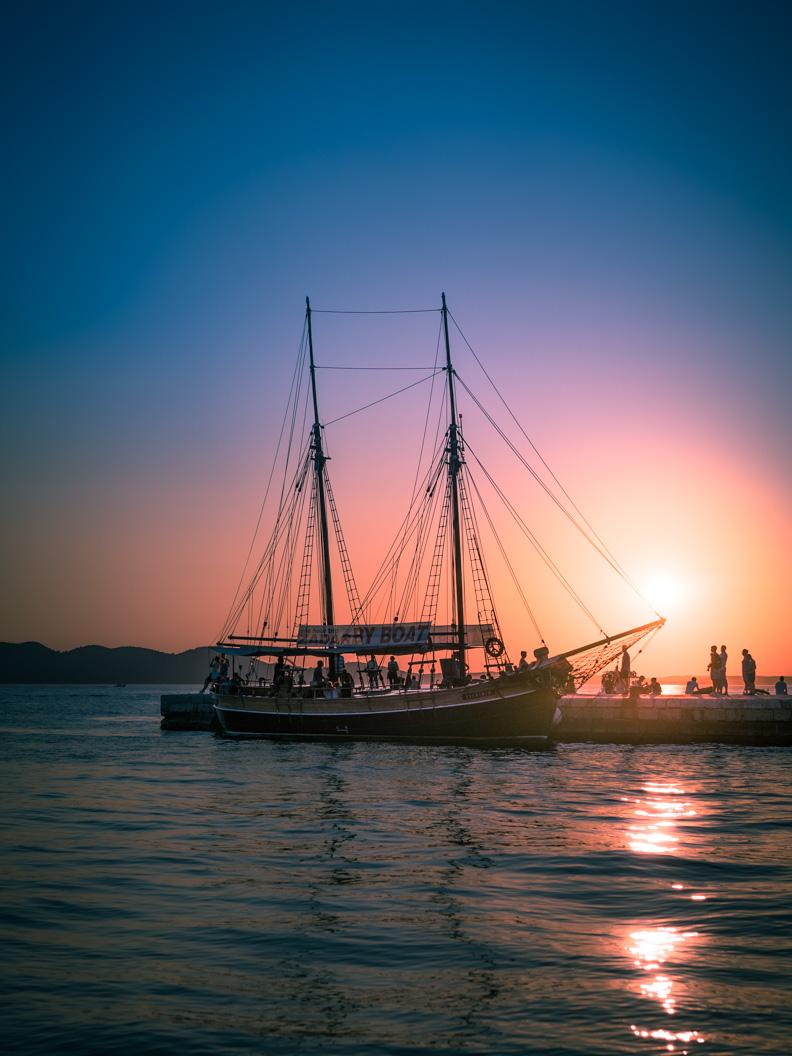 Ein Seegelschiff vor dem Sonnenuntergang in Zadar