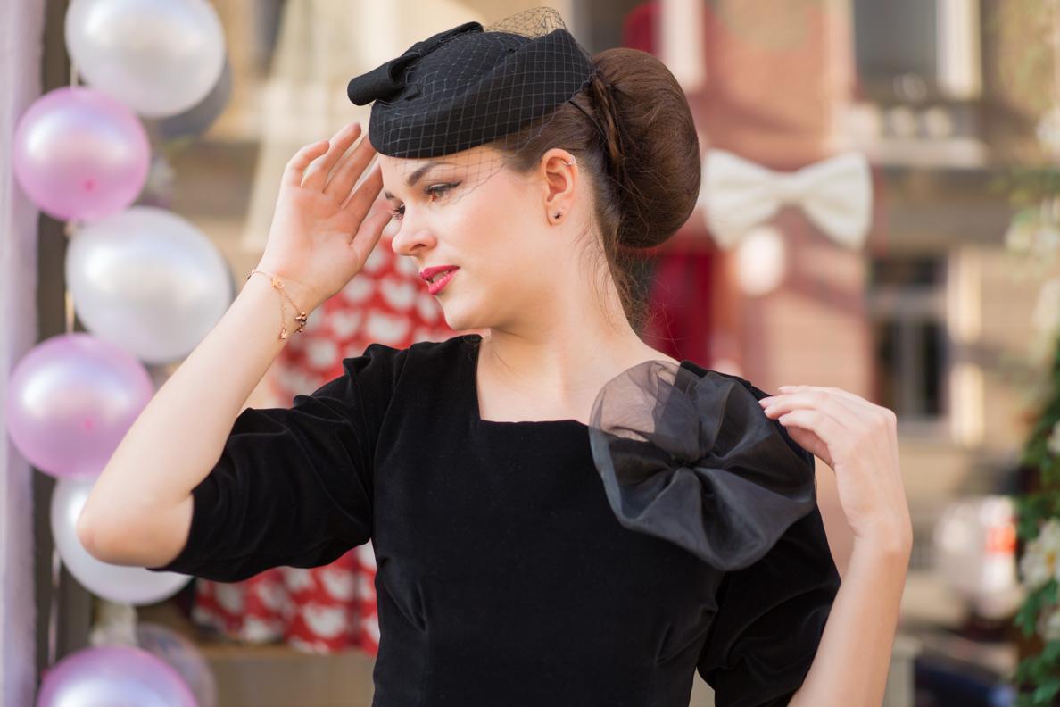 Vintage-Bloggerin RetroCat mit schwarzem Samtkleid und Hut