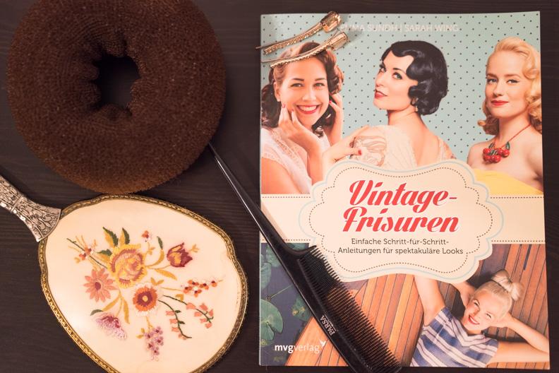 """Das Buch """"Vintage-Frisuren"""", ein Duttkissen, Spiegel und Kamm"""