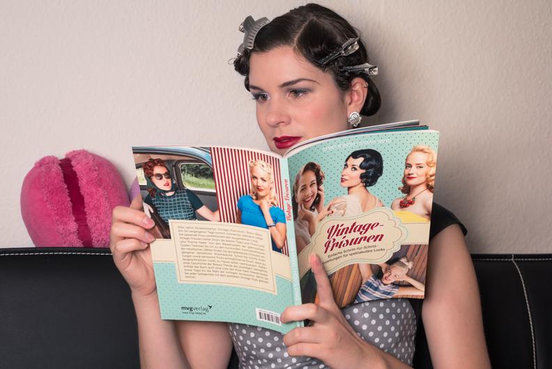 """RetroCat mit dem Buch """"Vintage-Frisuren"""" beim Lesen und Stylen der Haare"""