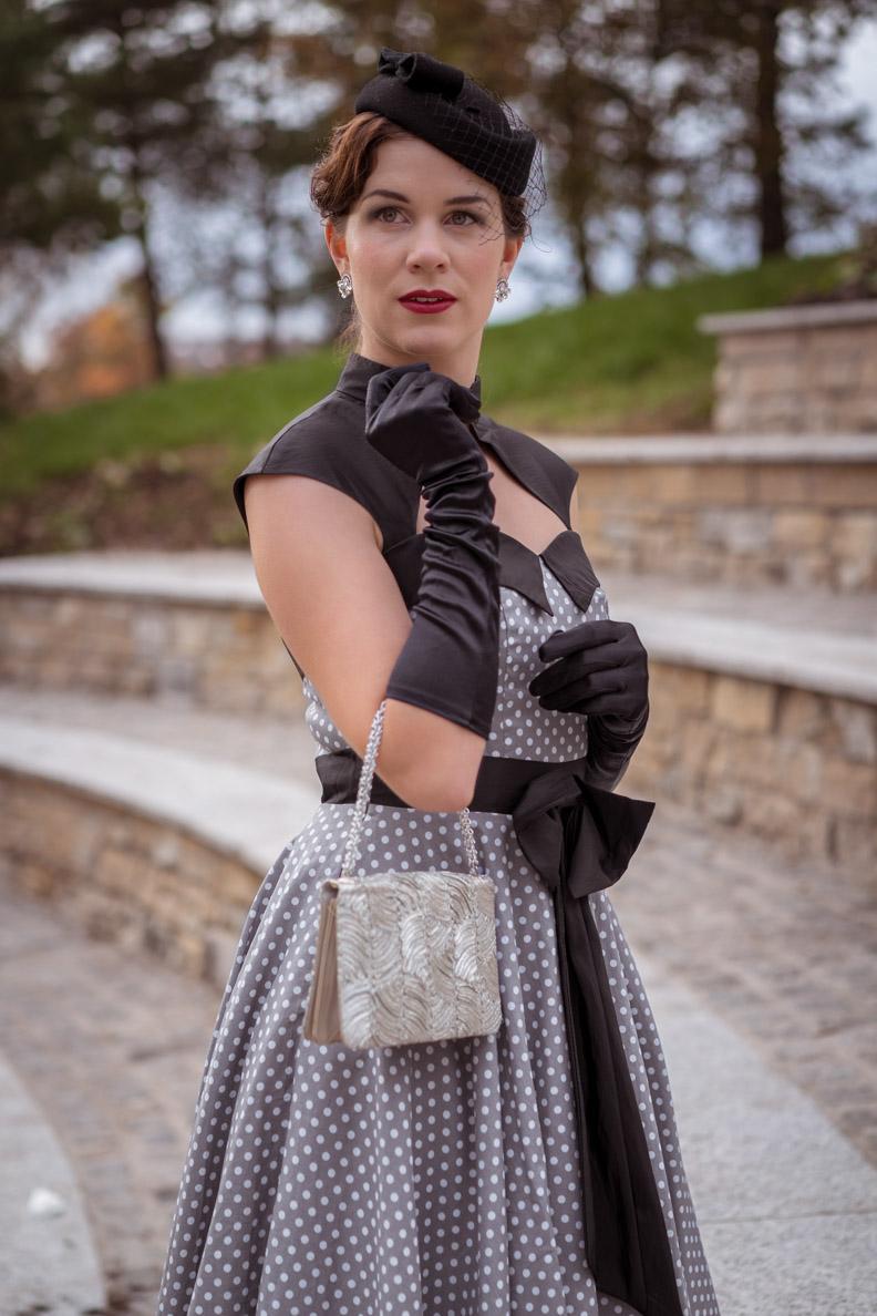 RetroCat mit Vintage-Tasche, langen Handschuhen, Hut und Retro-Kleid