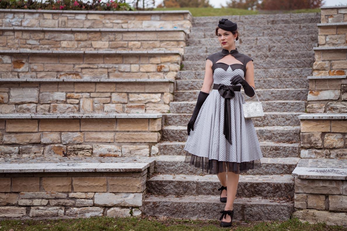Vintage-Bloggerin RetroCat in einem eleganten grauen Retro-Kleid mit weißen Punkten