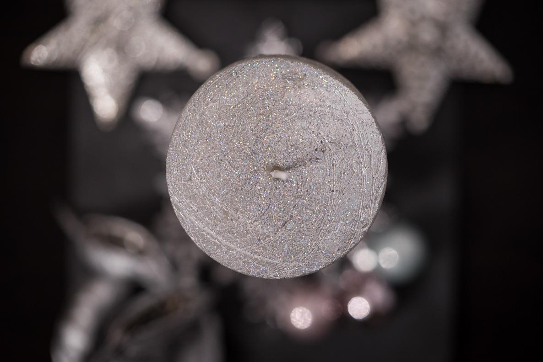 Eine silberne Kerze als Mittelpunkt eines weihnachtlichen Gestecks