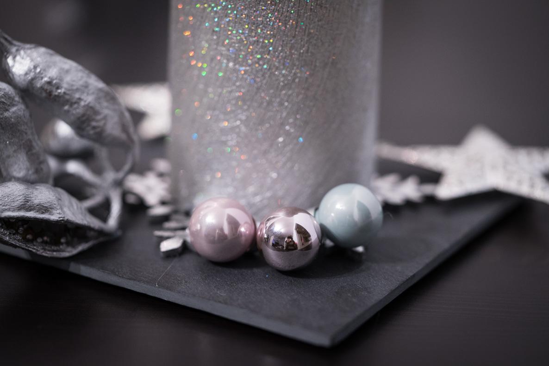 Kleine Weihnachts-Kugeln als Dekoration auf einem Gesteck
