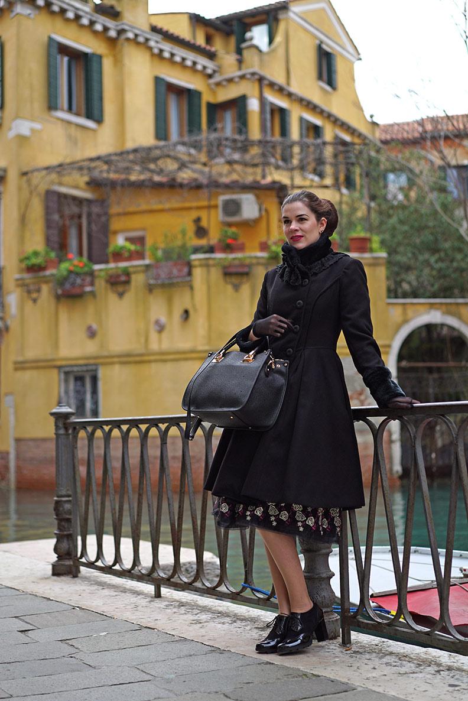 Vintage-Bloggerin RetroCat in einem schwarzen Mantel von Hell Bunny in Venedig