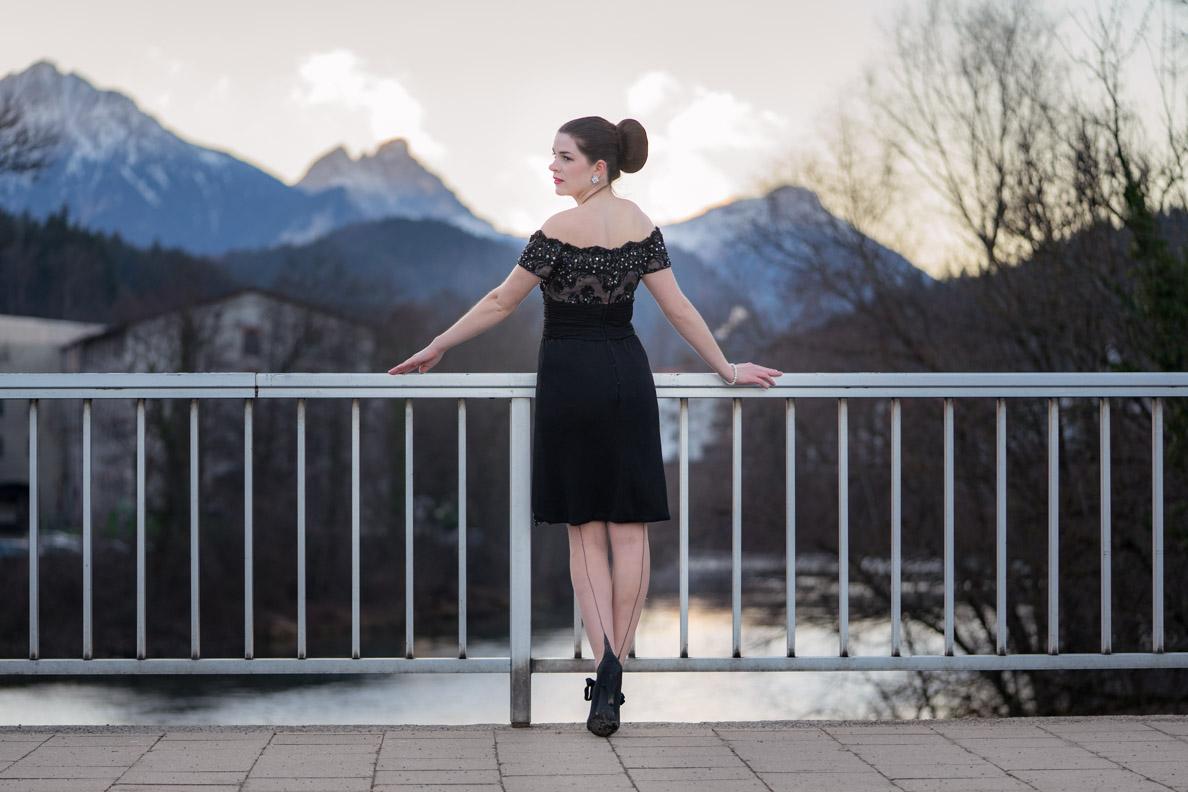 RetroCat mit glamourösem Vintage-Kleid, großem Dutt und Nahtstrümpfen