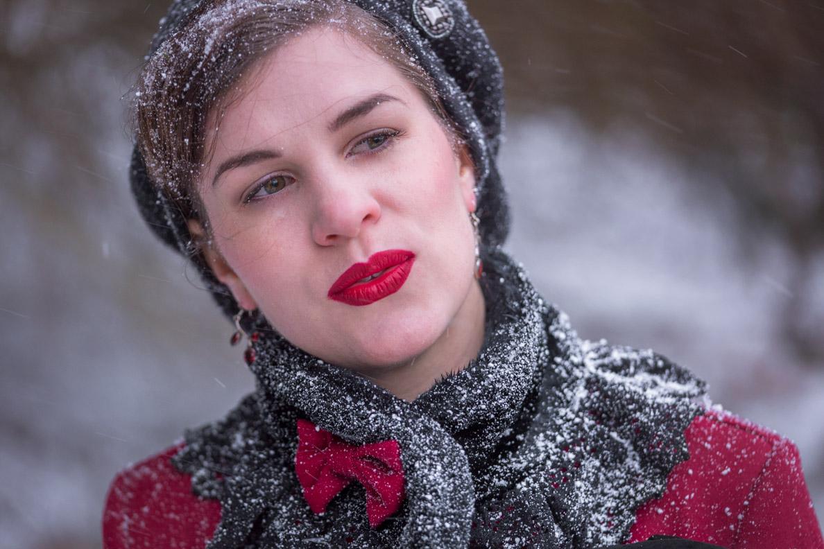 Bloggerin RetroCat mit Barett, rotem Lippenstift und kuscheligem Retro-Mantel