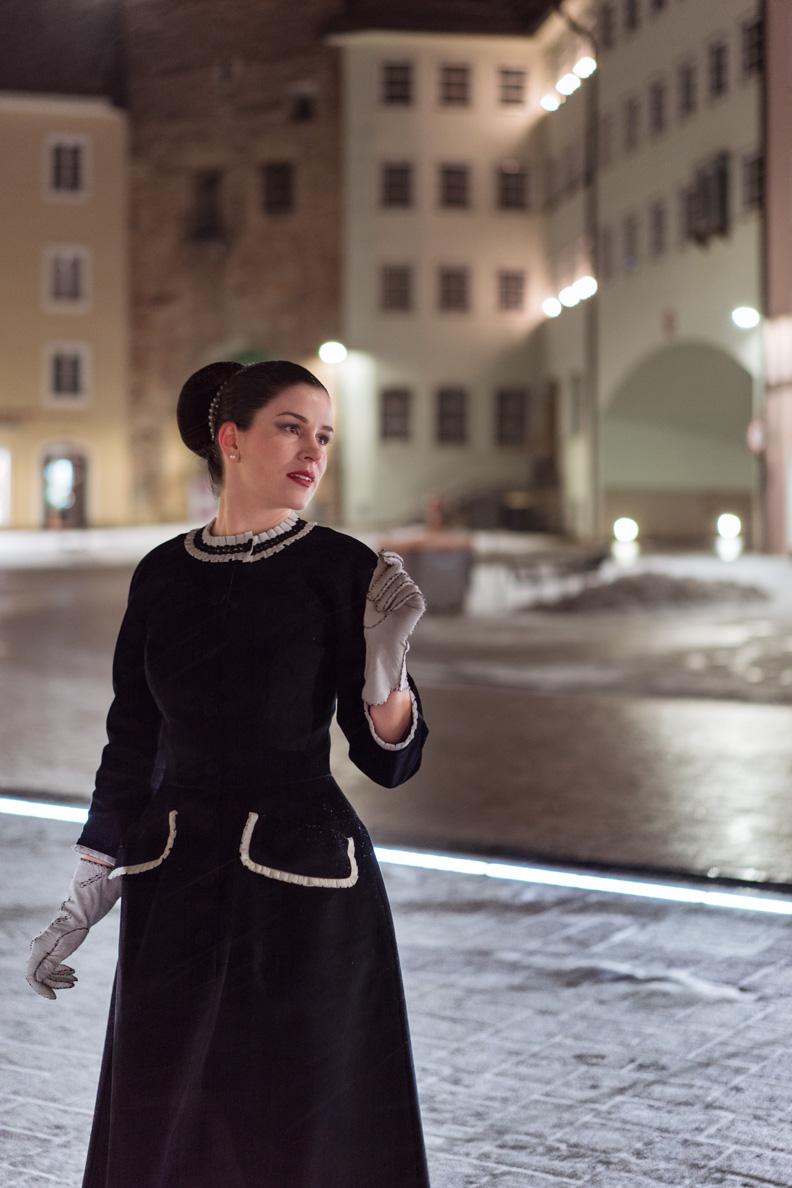 RetroCat in einem schwarzen Retro-Kleid mit weißen Rüschen-Details