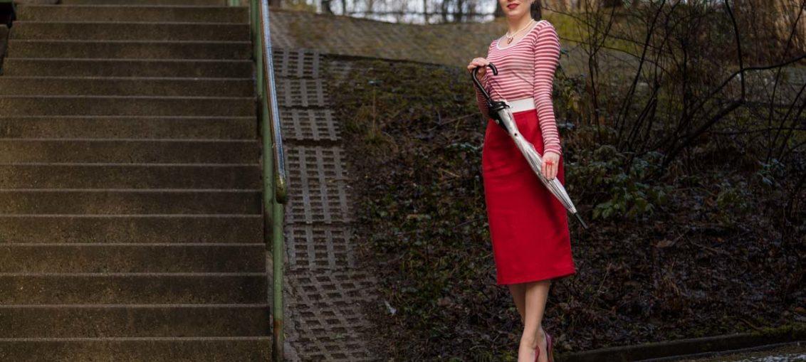 Für nasskaltes Wetter: Ein Regenschirm und roter Rock im Retro-Stil