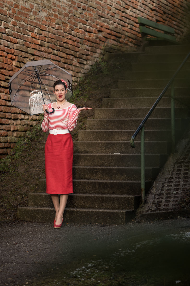 RetroCat mit rotem Bleistiftrock, transparentem Regenschirm und Lackpumps