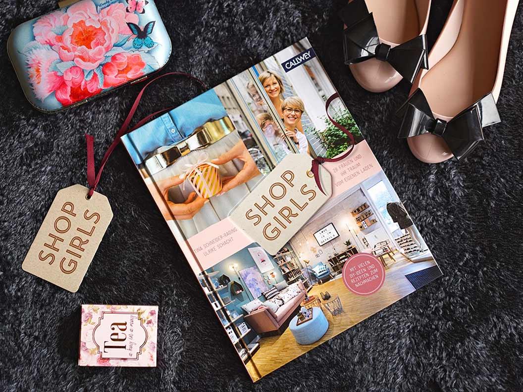 """Ein Flatlay mit dem Buch """"Shop Girls"""", einer Handtasche sowie Ballerinas"""