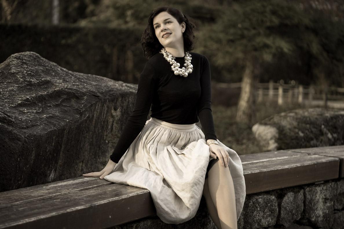 Vintage-Bloggerin RetroCat mit beigem Rock und schwarzem Oberteil