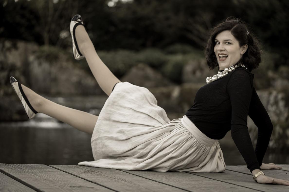 Bloggerin RetroCat mit schwarz-weißen Ballerinas, beigem Rock und schwarzem Oberteil