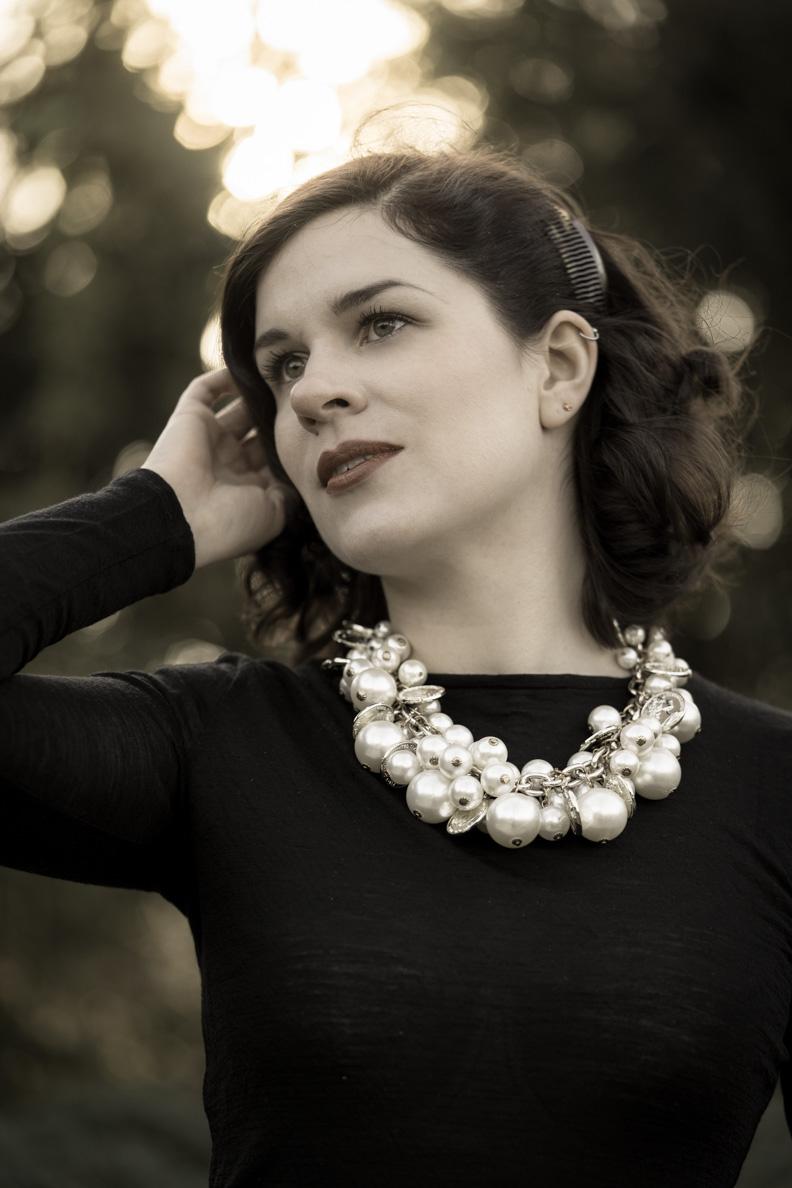 RetroCat mit einer großen Perlenkette im Stil von Coco Chanel