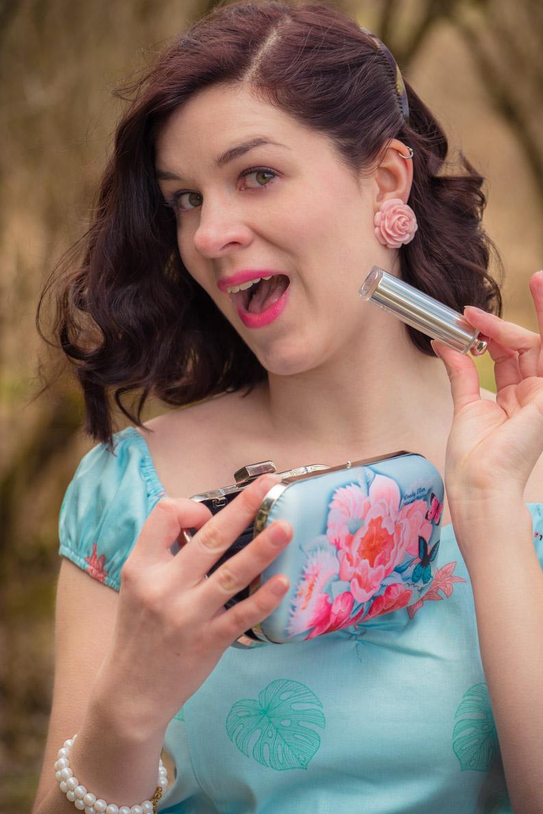 RetroCat mit hellblauem Retro-Top, Woody-Ellen-Tasche und Dior-Lippenstift in Pink