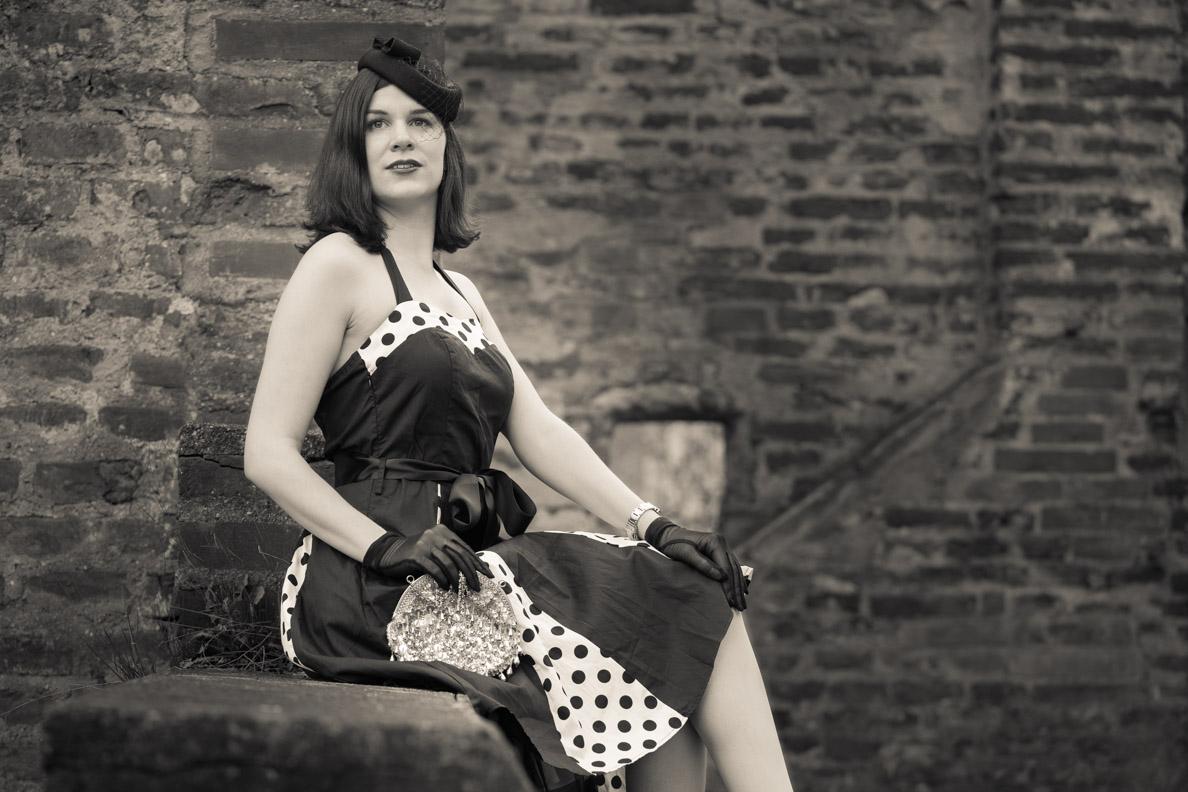 """RetroCat mit dem Kleid """"Ivy"""" von BlackButterfly und einer glitzernden Vintage-Tasche"""