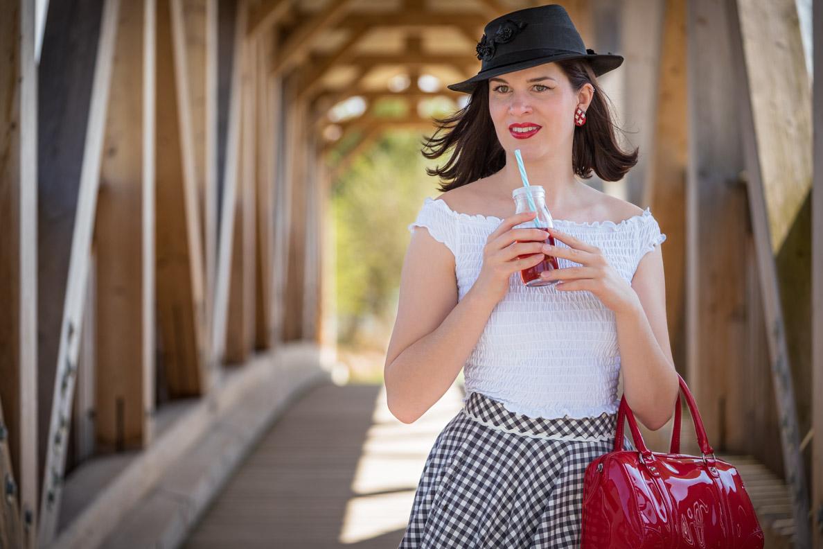 Sandra vom Vintage-Blog RetroCat mit Strohhut und Trinkflasche im Retro-Stil
