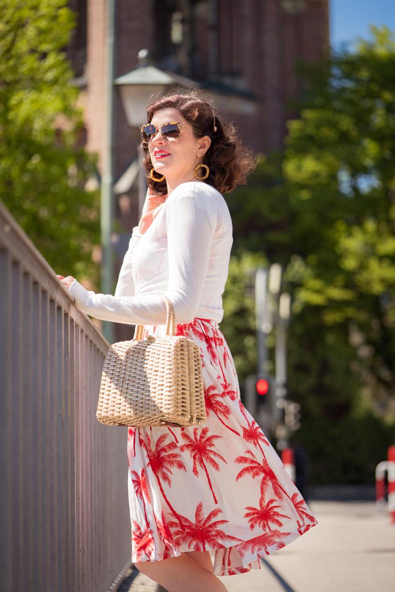 RetroCat mit dem Palm Dress, einem weißen Cardigan und einer Vintage-Handtasche
