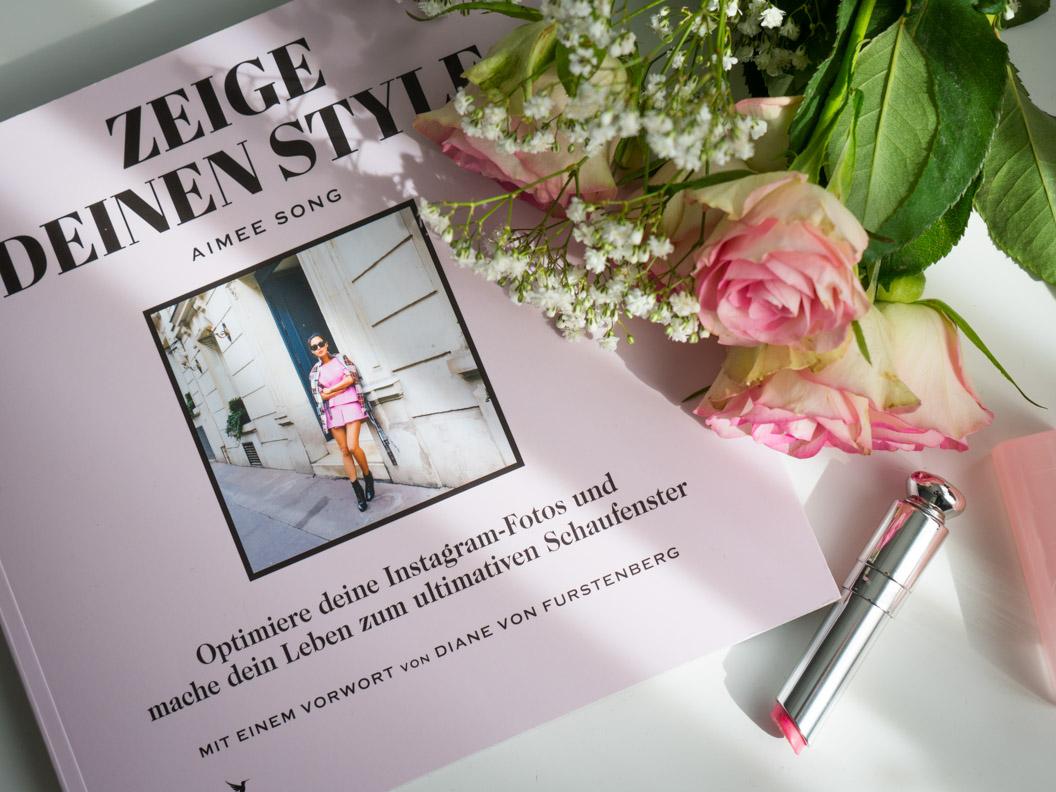 """Ein Flatlay bestehend aus dem Buch """"Zeige Deinen Style"""", Rosen und einem Dior-Lippenstift"""