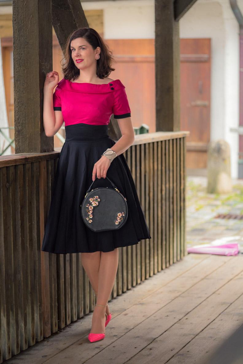 RetroCat mit einem klassischen Retro-Kleid und pinken Accessoires