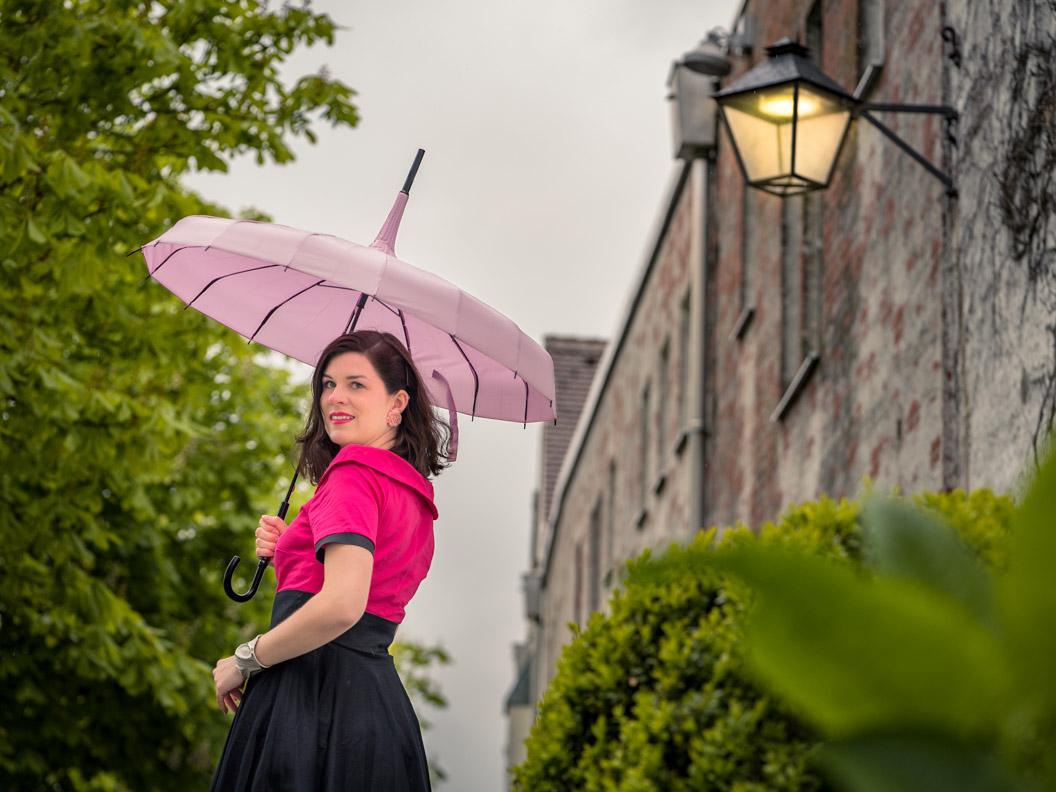 Vintage-Bloggerin RetroCat mit Retro-Kleid und Pagoden-Schirm im Regen