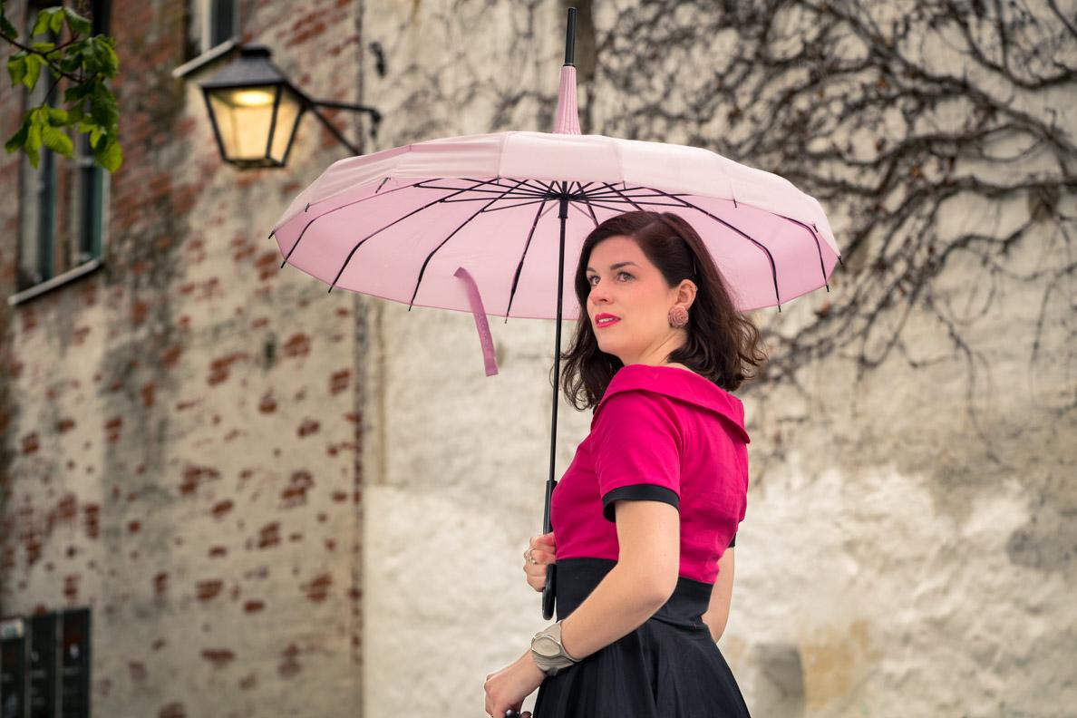 Fashion-Bloggerin RetroCat mit einem rosa Regenschirm und pinkem Make-up