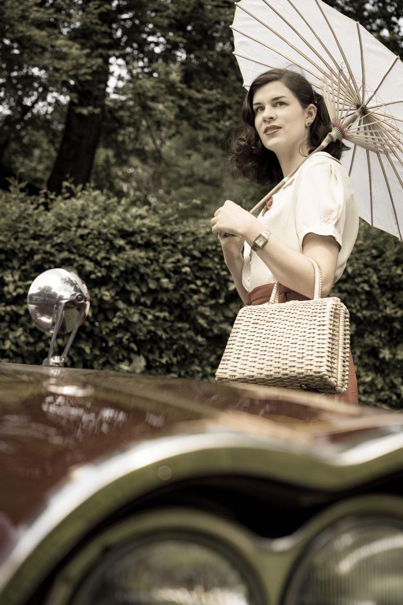 RetroCat mit einem 40er-Jahre-Outfit und einer Vintage-Handtasche