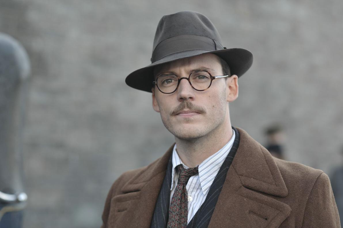 """Sam Claflin alias Tom Buckley in einem klassischen Anzug im Film """"Ihre beste Stunde"""""""
