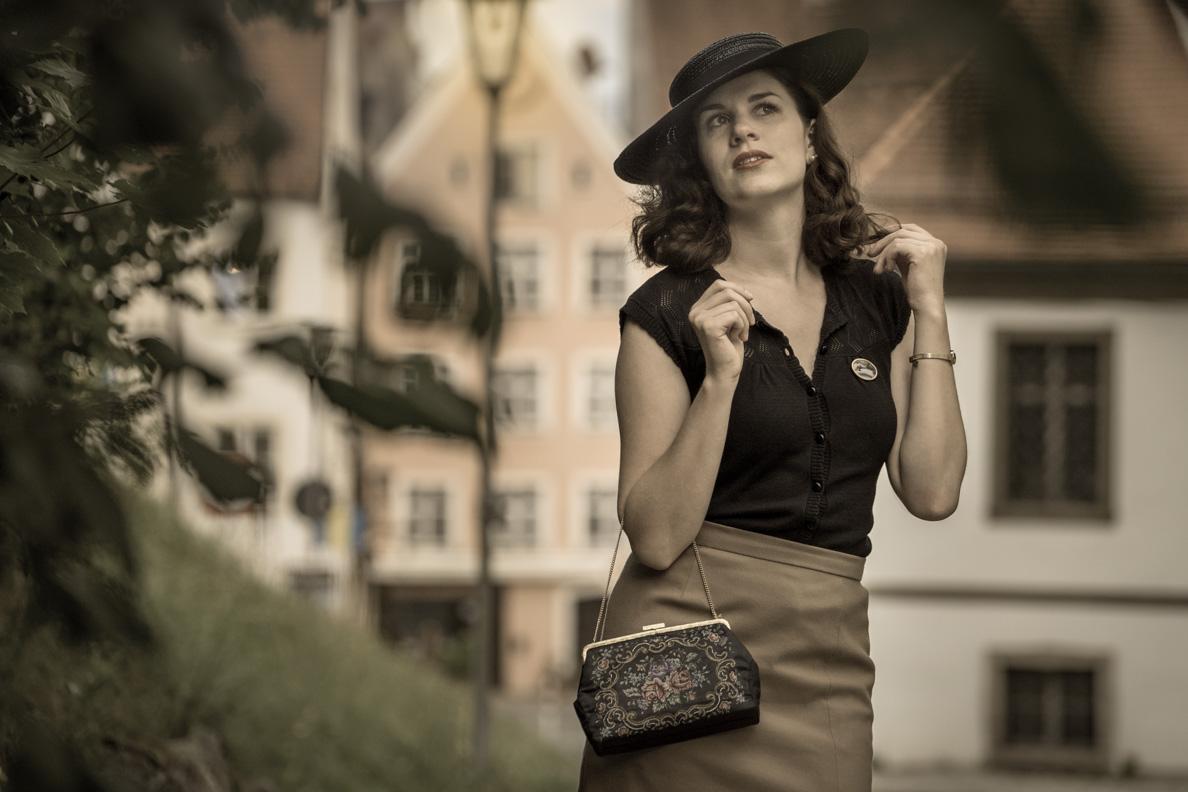 RetroCat mit einem großen Vintage-Hut und einer Gobelin-Tasche
