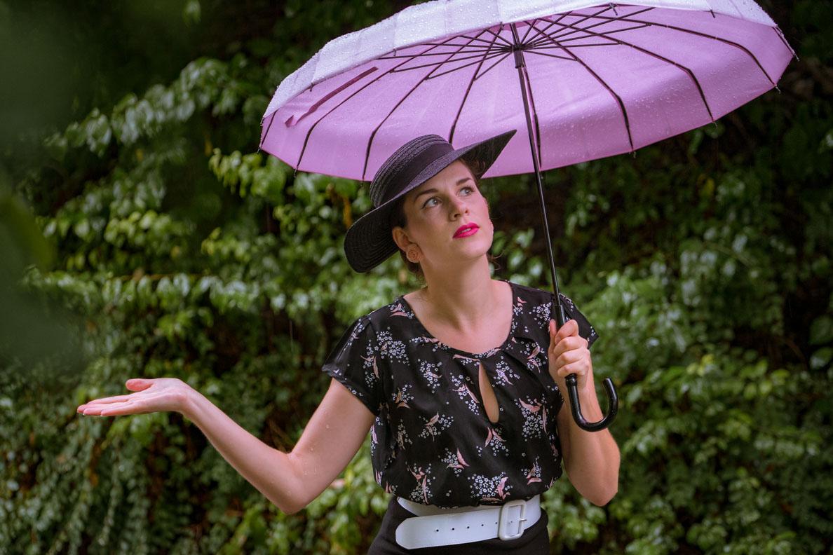 RetroCat mit Bluse, Vintage-Hut und pinken Accessoires im Regen