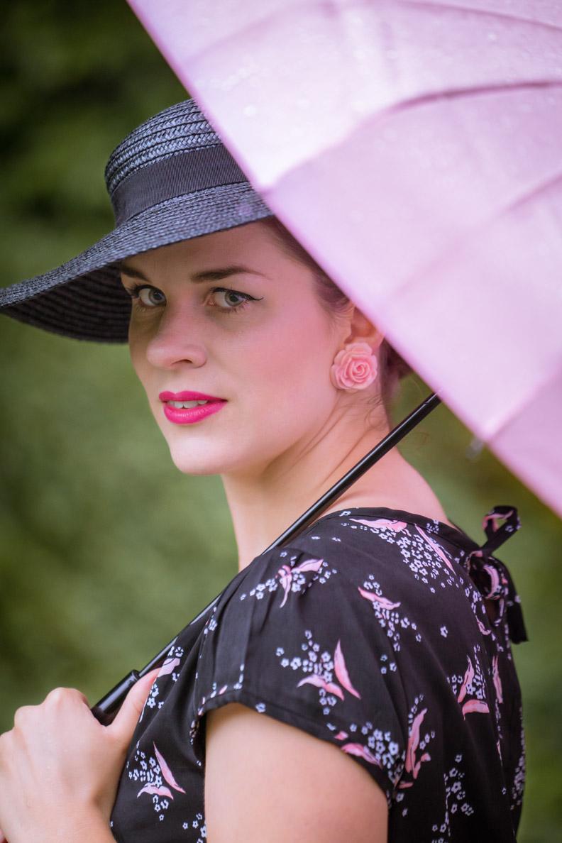 RetroCat mit Vintage-Hut, Rosen-Ohrringen und rosa Regenschirm