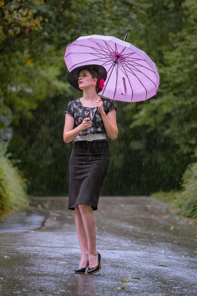 Vintage-Bloggerin RetroCat mit Bleistiftrock, Retro-Bluse und rosa Regenschirm