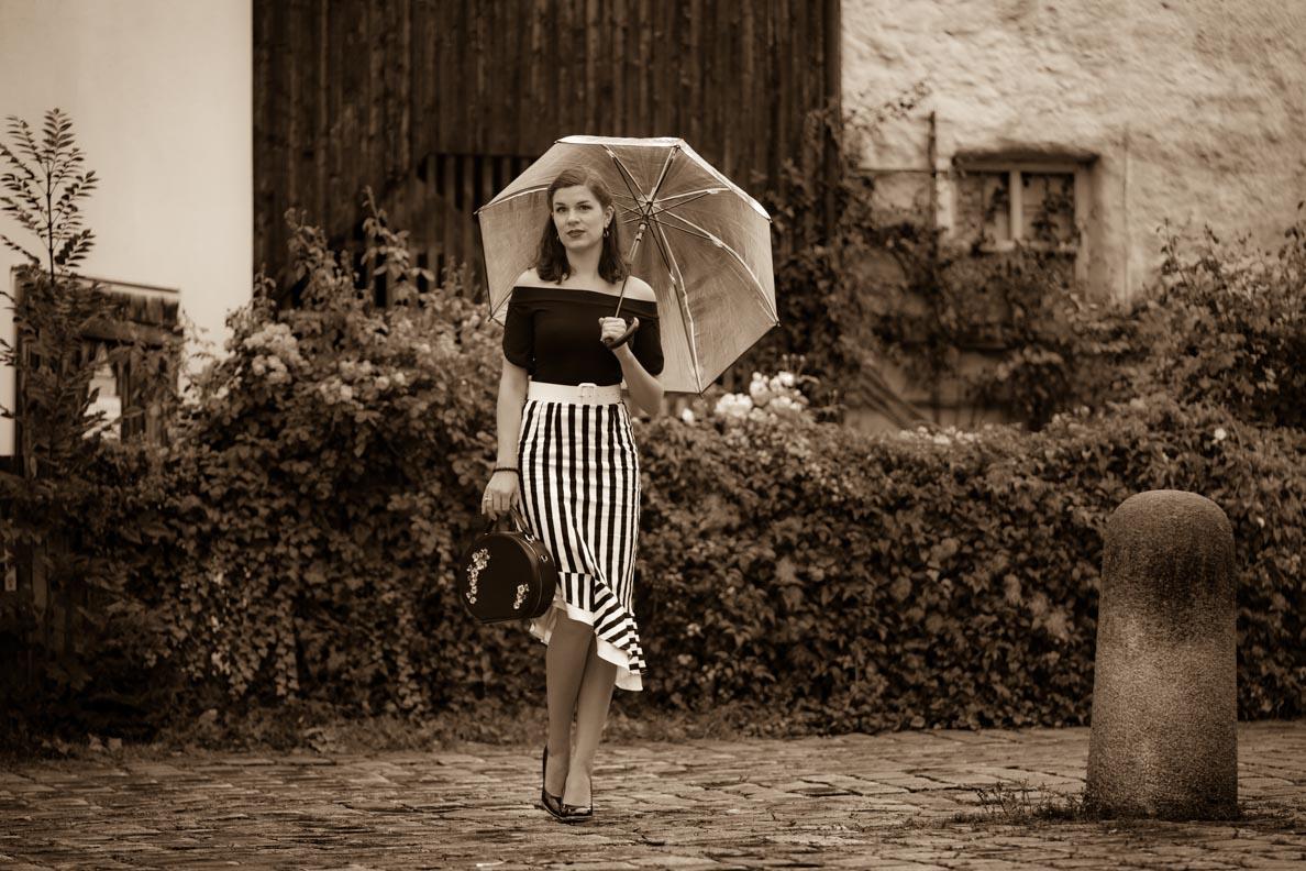 RetroCat mit Regenschirm, Streifenrock und Top im Vintage-Stil