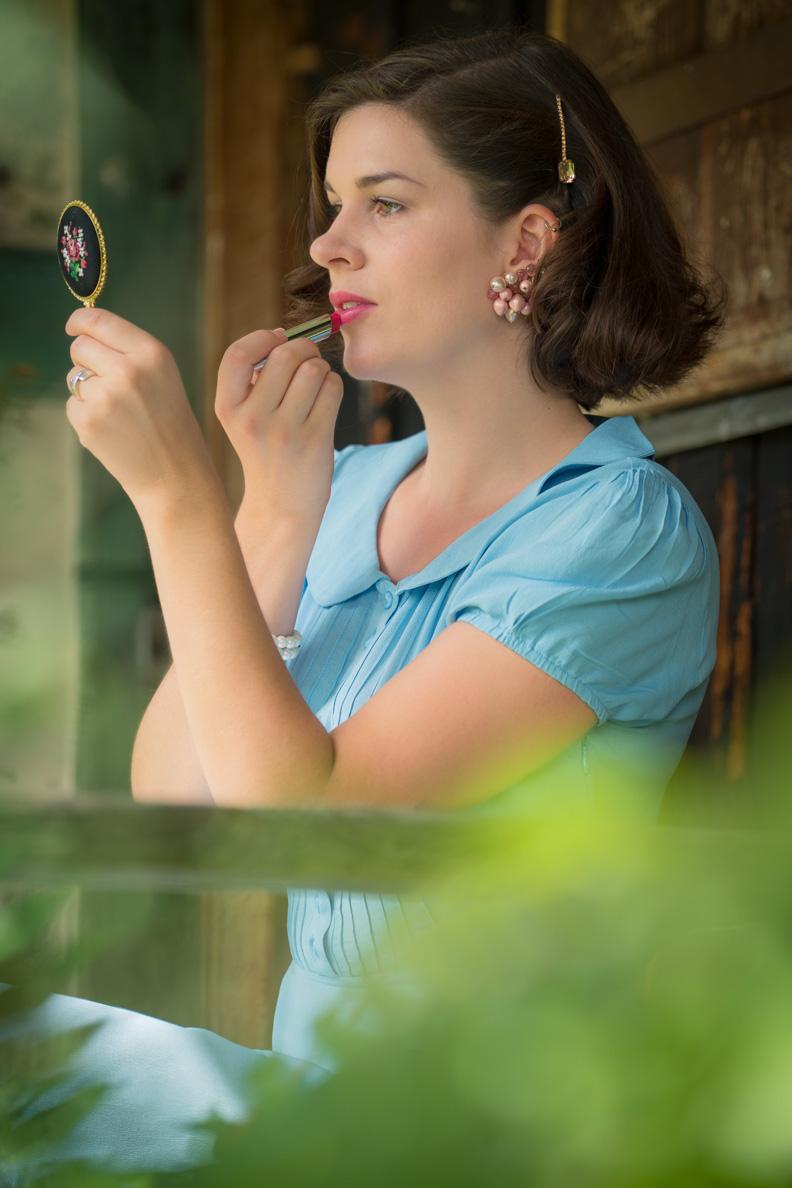 Beauty-Bloggerin RetroCat mit Vintage-Spiegel und Dior-Lippenstift