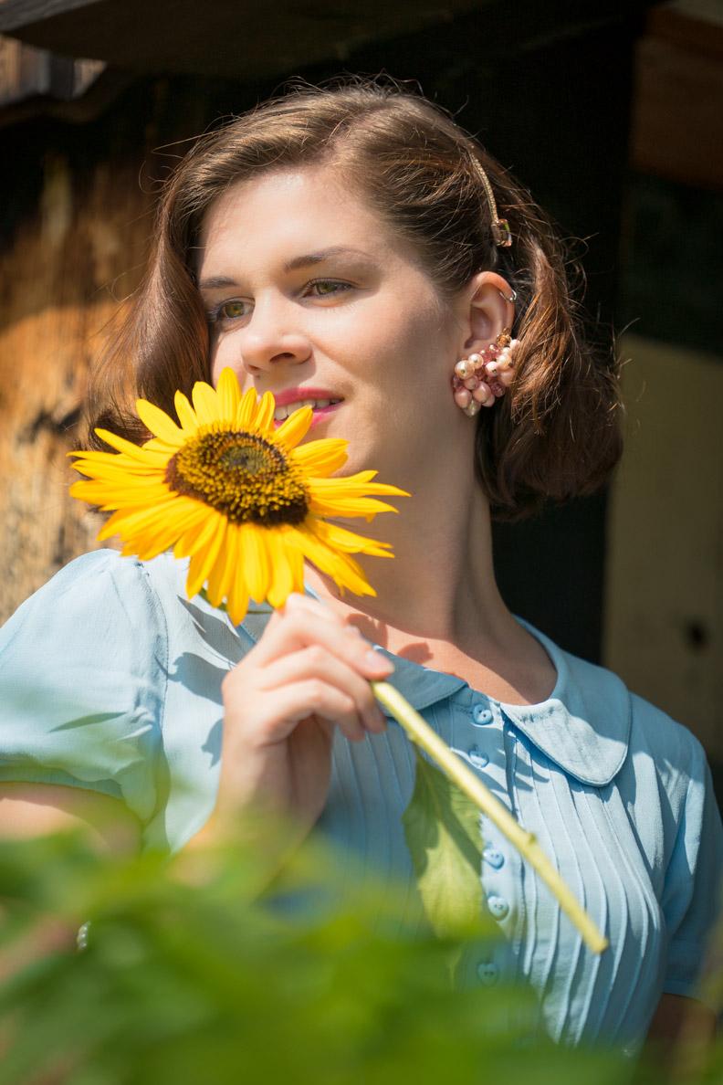 RetroCat mit rosafarbenen Vintage-Ohrringen und Sonnenblume