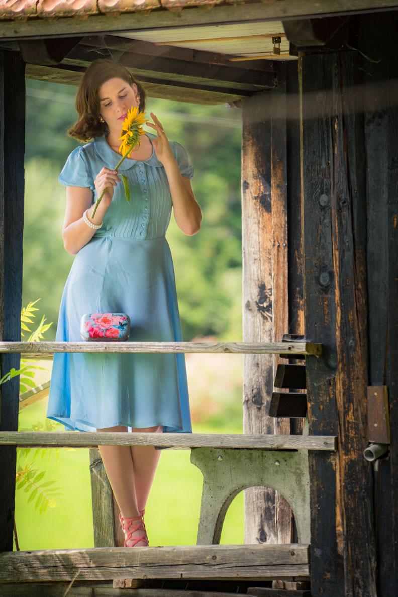 RetroCat mit Sonnenblume, 40er-Jahre-Kleid und einer Clutch von Woody Ellen