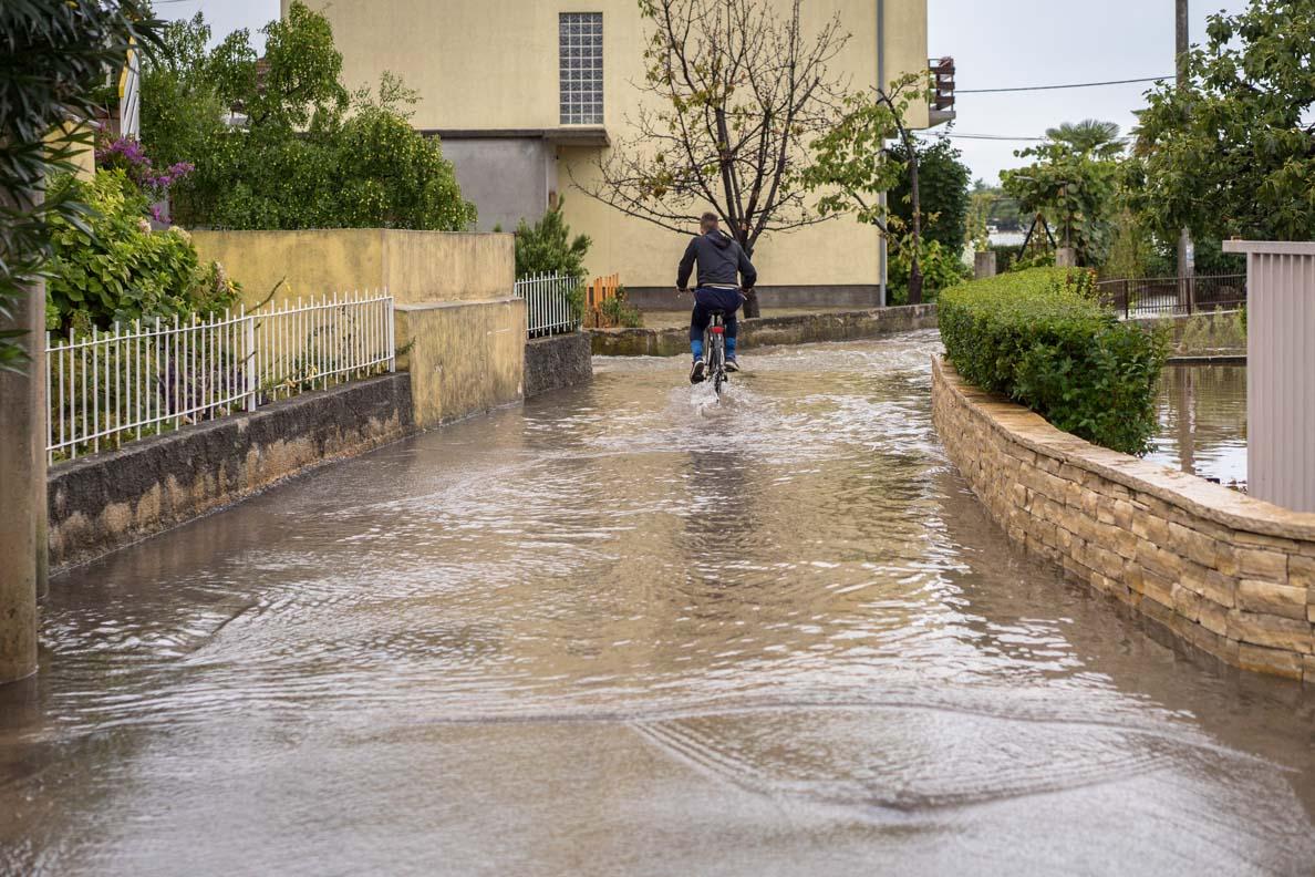 Ein Fahrradfahrer auf einer überfluteten Straße in Norddalmatien