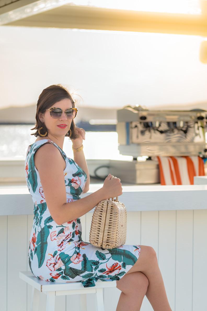 RetroCat mit Retro-Kleid und Vintage-Handtasche an einer Strandbar